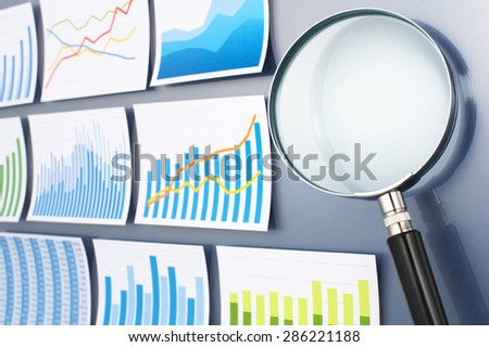 Many graphs and magnifying glass on dark blue background. Researching and analyzing data with magnifying glass. Trend survey.  - stock photo