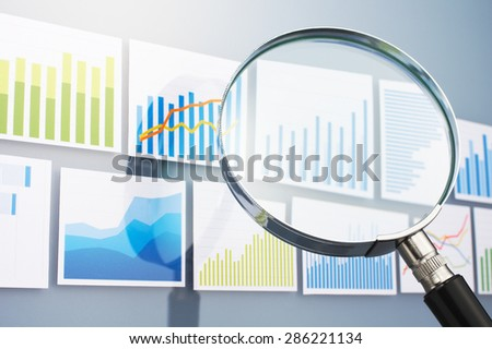 Many graphs and magnifying glass on gray background. Searching and analyzing data with magnifying glass. Situation analysis.  - stock photo