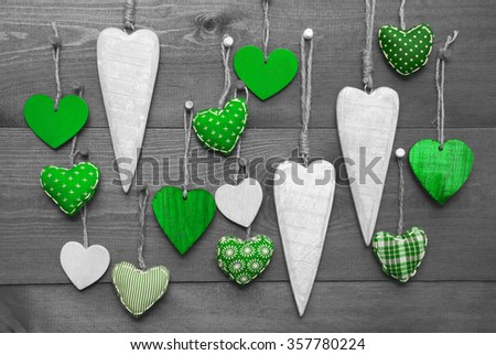 Many Green Hearts Hanging Infront Of Wooden Background. Black And White Image With Colored Hot Spots. Romantic Decoration For Valentines Day. Rustic, Retro Or Vintage Style - stock photo