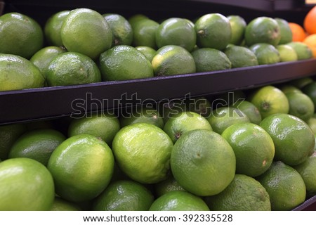 Many green limes on the shelf. Close up