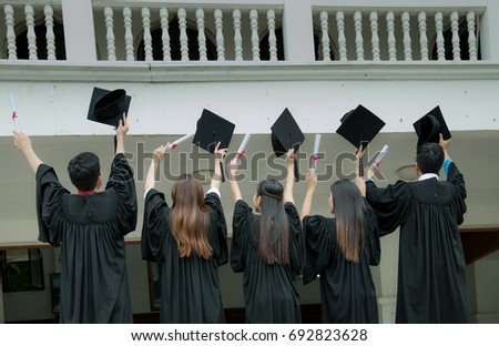 Many hand holding graduation hats on building background,