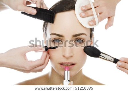 many hands applying make up on a womans face - stock photo