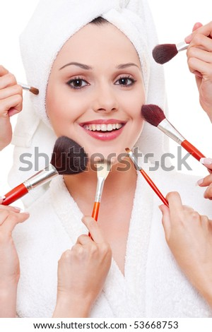 many hands applying make-up to beautiful smiley woman - stock photo