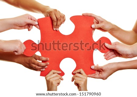Many hands holding a big red jigsaw puzzle piece - stock photo