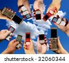 Many hands holding mobile phones - stock photo