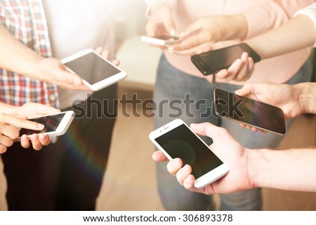 Many hands holding mobile phones close up - stock photo