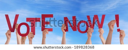 Many Hands Holding the Red Words Vote Now in the Sky - stock photo