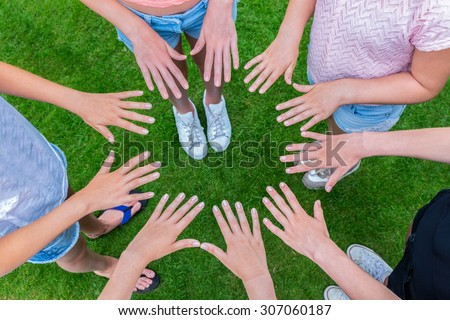 Many hands of young girls making circle above green grass