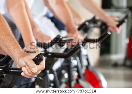 Many hands on bikes in fitness center - stock photo