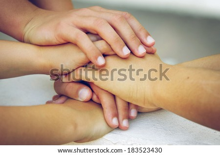 Many hands piled on top of one another in a sign of trustful friendship  - stock photo