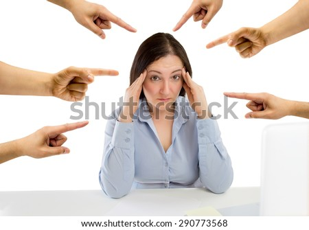 many hands pointing the overwhelmed woman that is suffering  mobbing in the workplace  - stock photo