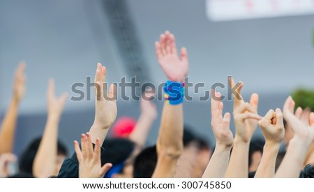 Many hands raised in a crowd of people - stock photo