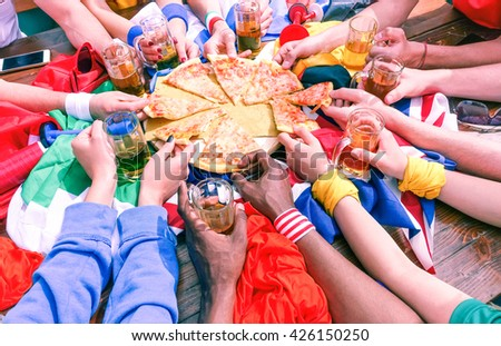Many hands sharing pizza view from above - Multicultural sport fans arms on party table  at cafe bar eating and drinking together - Concept of international friendship fun and sportive events meeting  - stock photo