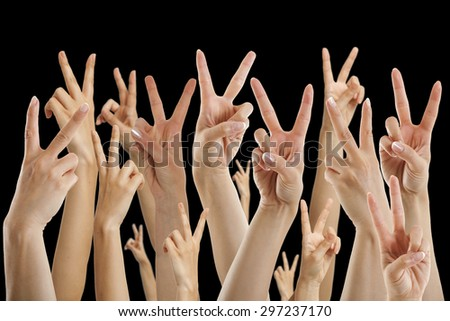 many hands showing victory sign, isolated on black - stock photo