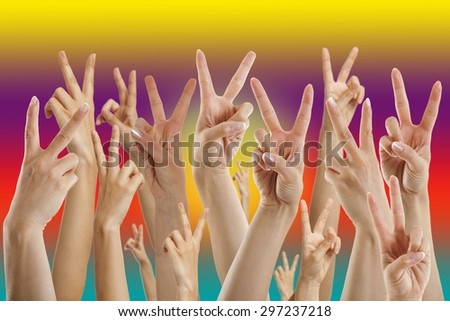 many hands showing victory sign, multicolors background - stock photo