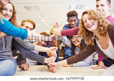 Many hands stacked as symbol for teamwork in a university class - stock photo