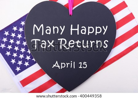 Many Happy Tax Returns message on heart shaped blackboard with USA Stars and Stripes flag for Tax Day, April 15.