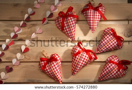 many hearts sewn from red plaid fabric on the board, a symbol of love