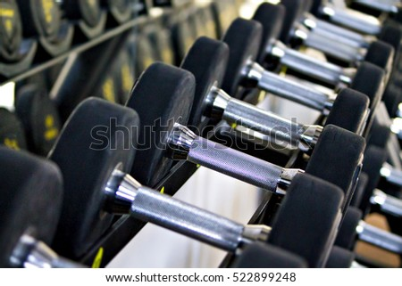 Many heavy barbells in the gym on the shelf.