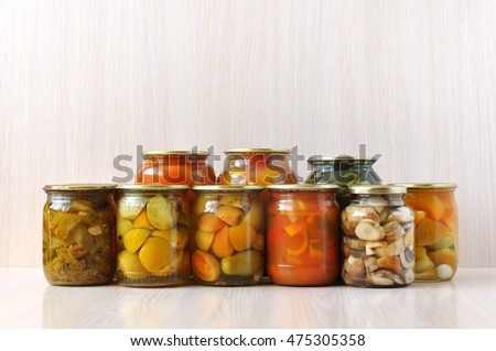 Many inverted glass jars with canned pickled vegetables on wooden surface: peppers, tomatoes, cucumbers, mushrooms.