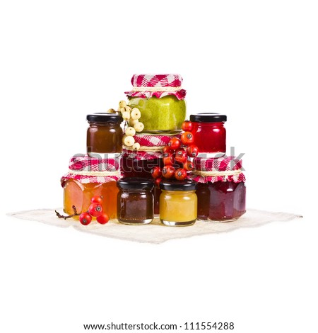 Many jars of various sizes with marmalade of different colors isolated on white background - stock photo