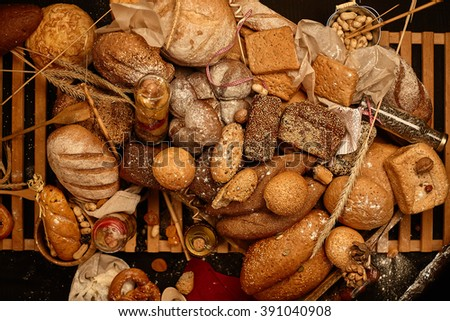 Many kinds of fresh baked bread, jars with pickles, wheat ear, dried fruits and cereals on a wooden trellis. White and brown bread, baguette and whole grain bread.