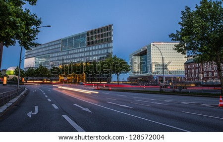 Many lanes of the street separates viewer from the modern glass- and steel-made buildings. - stock photo
