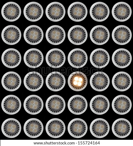 Many LED Light bulbs in pattern with only one illuminated and taken from above and isolated against black - stock photo