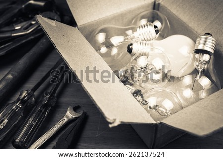 Many light bulbs in cardboard box with tools