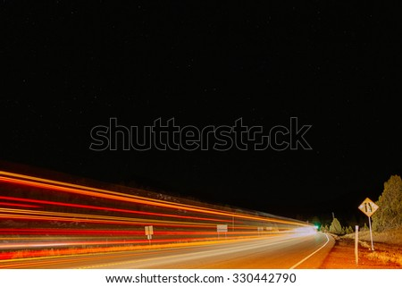 Many lights of a fast moving vehicle swoosh past on a desert road on a starry night