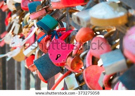 Many marriage love symbol padlocks chained on bridge in Astrakhan Russia. - stock photo