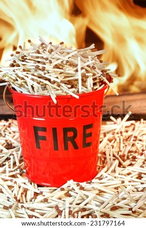 Many Matches Around and In the Fire Bucket. Fire Flames in Background. Concept: DO NOT PLAY WITH FIRE, Dangerous - stock photo