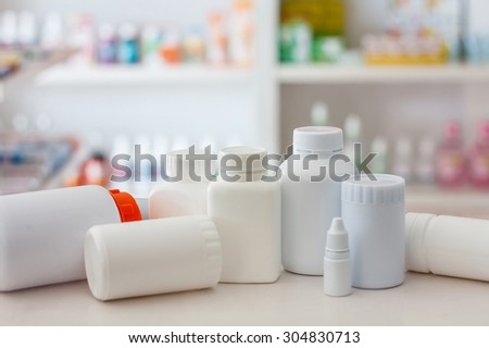 many medicine bottle with blur shelves of drug in the pharmacy drugstore background