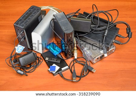 Many memory devices like hard disk drives or memory cards, in format USB or Firewire, with a lot of entangled cables - stock photo