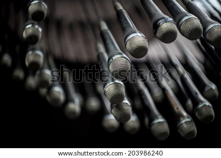 many microphones hanging from the ceiling - stock photo