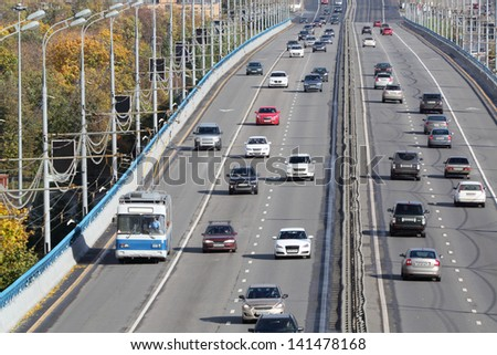 Many modern cars go on bridge at sunny day in Moscow, Russia. - stock photo