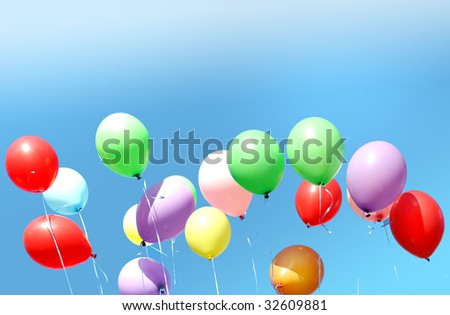 Many multi-colored balloons on a background of the blue sky - stock photo