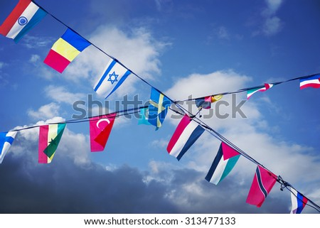 many nation flags on blue sky, symbolizing unity and cooperation