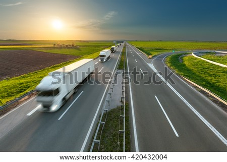 Many new modern trucks in a row driving towards the sun at idyllic sunny day. Fast blurred motion drive on the freeway. Freight scene on the motorway near Belgrade, Serbia. - stock photo