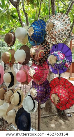 Many of Beautiful hats hang on stall at shop atmosphere in the garden.  - stock photo
