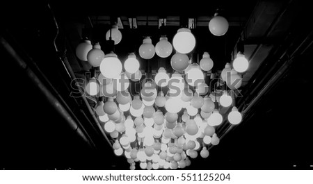 Many of Decorative light lamp bulb glowing on the ceiling - Black and White