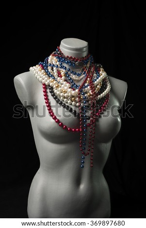Many of miscellaneous pearl necklace on gray mannequin over black backgrounds - stock photo