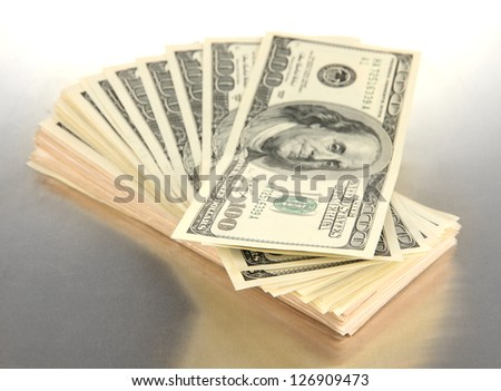 Many of one hundred dollars banknotes close-up on grey background