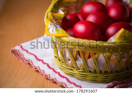 Many of Red Easter Eggs in a Yellow Basket on a Wooden Table