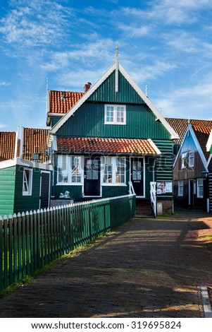 Many of the wooden houses in Marken are painted green and have orange roof tiles giving the village itâ??s typical appearance and cozy idyllic atmosphere - Follow the green painted fence to the house