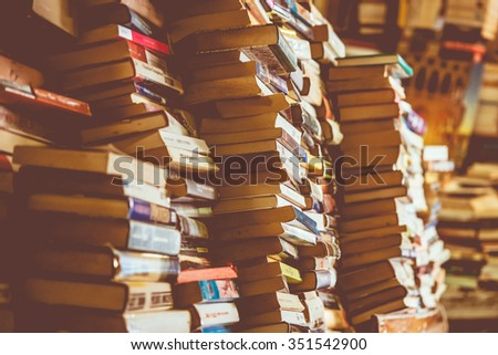 Many old books in a book shop, fair or library. Toned picture - stock photo