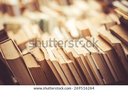 Many old books in a book shop or library. Toned image. Shallow DOF - stock photo