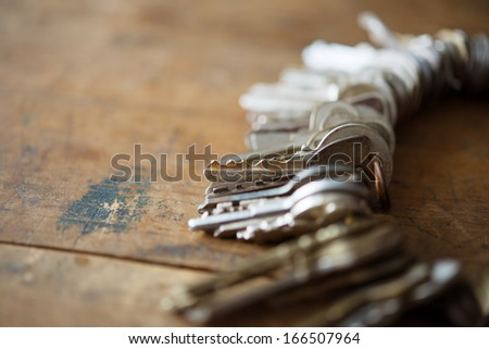 Many old keys on a well used old wooden desk. Security and encryption, concept image. - stock photo