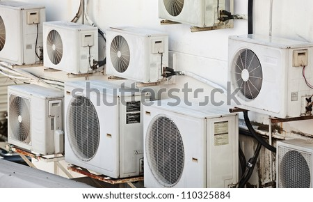 Many older air conditioners on the wall - stock photo