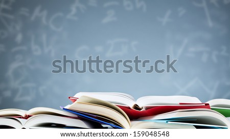 Many open books lying flat before a blue background with various formulas and letters. - stock photo